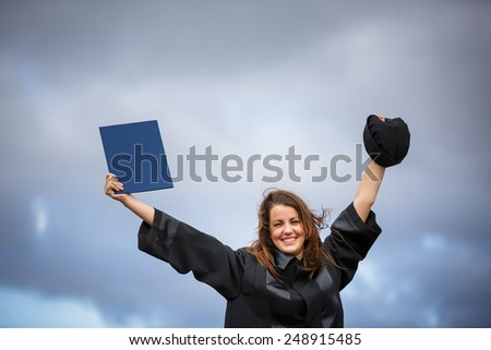 Pretty, young woman celebrating joyfully her graduation - spreading wide her arms, holding her diploma, savouring her success (color toned image; shallow DOF) - stock photo
