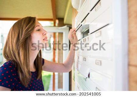 Pretty, young woman checking her mailbox for new letters - stock photo