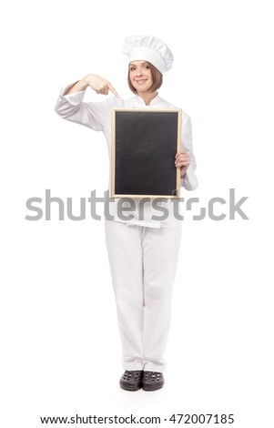 pretty young woman chef, cook or baker holding empty blackboard for your text and pointing on it isolated on white background. restaurant, dieting and cooking food concept