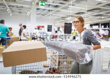 Pretty, young woman choosing the right furniture for her apartment in a modern home furnishings store - with a trolley, done shopping, leaving the store, going home with the purchased goods