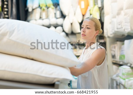 pretty young woman choosing the right item for her apartment in a modern home decor