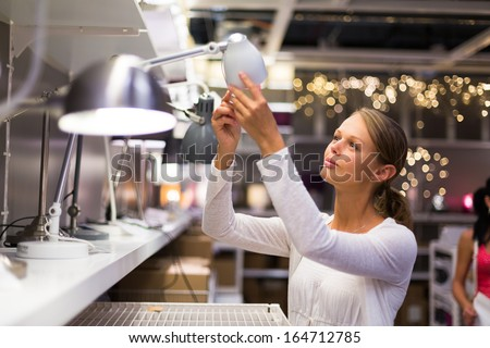 Pretty, young woman choosing the right lamp for her apartment in a modern home furnishings store (color toned image; shallow DOF) - stock photo