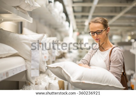 Pretty, young woman choosing the right pillow for her bed in a modern home furnishings store (color toned image; shallow DOF) - stock photo