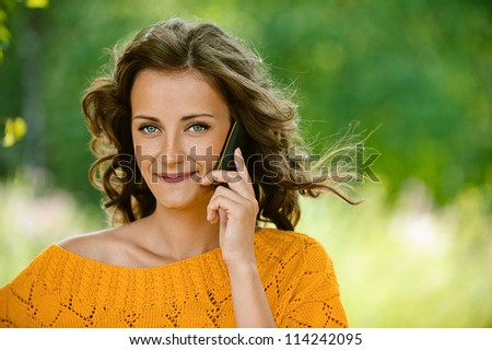 Pretty young woman close-up in orange sweater talking on cell phone, against green of summer park. - stock photo