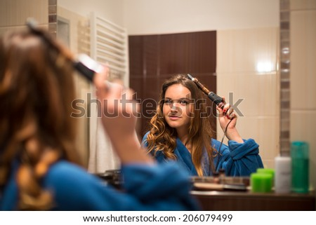 Pretty, young woman curling her hair in front of her bathroom mirror - stock photo