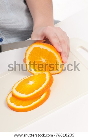 Pretty young woman cut orange. Isolated on the white background