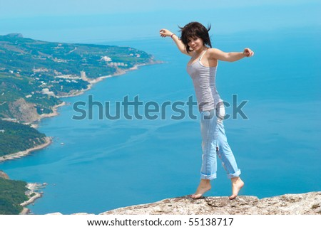 Pretty young woman, dancing on the rock - stock photo