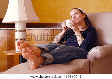 Pretty Young Woman Daydreaming on a Recliner With Coffee Cup - stock photo