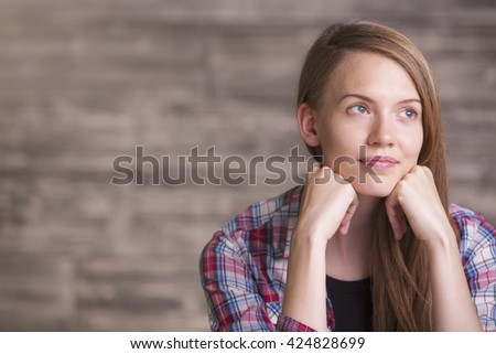 Pretty young woman daydreaming on blurry brown background - stock photo