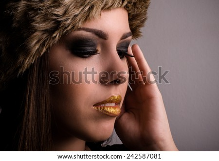 Pretty young woman displaying her dark modern eye makeup with her hand to her head, eyes closed and lips parted in a sensual close up beauty face portrait - stock photo