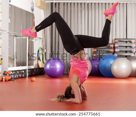 pretty young woman doing handstands  - stock photo