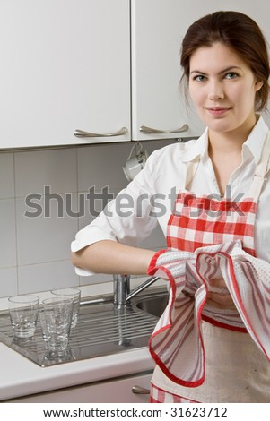 Pretty young woman doing housework in the kitchen - stock photo