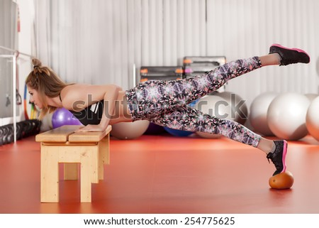pretty young woman doing push-ups on the bench and medicine ball  - stock photo