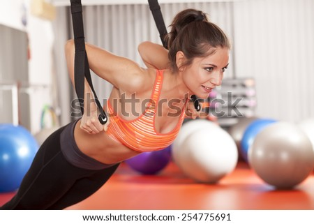 pretty young woman doing push ups with a hanging band  - stock photo