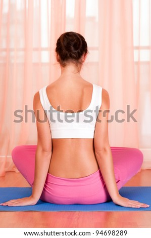 Pretty young woman doing yoga exercise on mat - stock photo