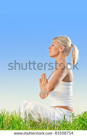 Pretty young woman doing yoga meditation exercising outdoors.