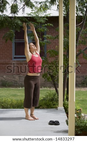 Pretty Young Woman doing Yoga on a Porch - stock photo