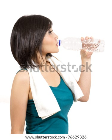 pretty young woman drinking a bottle of water after exercise - stock photo