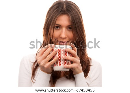 Pretty young woman drinking and  holding red pattern mug of tea coffee in hands isolated on white background - stock photo