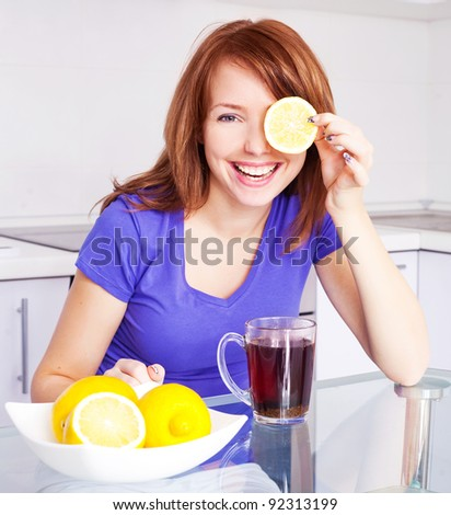 pretty young woman drinking black tea with lemons in the kitchen at home - stock photo