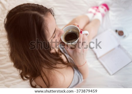 Pretty young woman drinking her coffee in the bed - stock photo