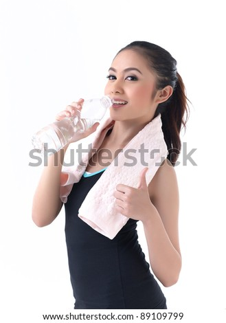 pretty young woman drinking water after exercise - stock photo