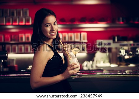 pretty young woman drinks cocktail in a night club