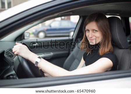 Pretty young woman driving her new car (shallow DOF; color toned image) - stock photo