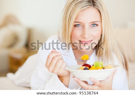 pretty young woman eating breakfast fruit salad on bed