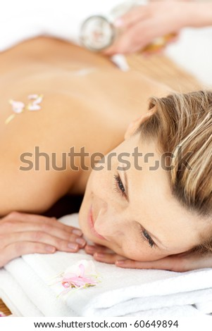 Pretty young woman enjoying a back massage with oil in a spa center