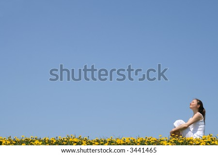 Pretty young woman enjoying sunshine and fresh air in a flowering field. - stock photo