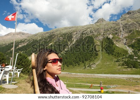 Pretty young woman enjoying the Swiss Alps in the summer. - stock photo