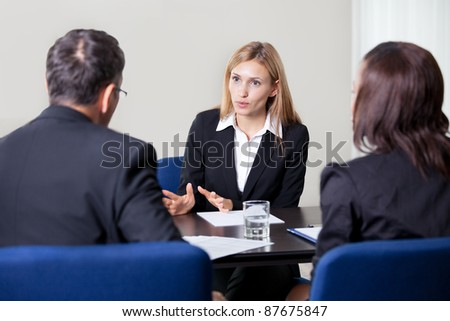 Pretty young woman explaining about her profile to business managers at a job interview - stock photo