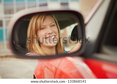 Pretty young woman face in car mirror - stock photo