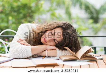 Pretty young woman fell asleep when doing homework - stock photo