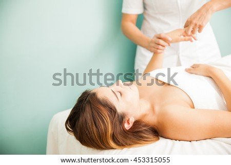 Pretty young woman getting a digitopuncture therapy session at a health spa