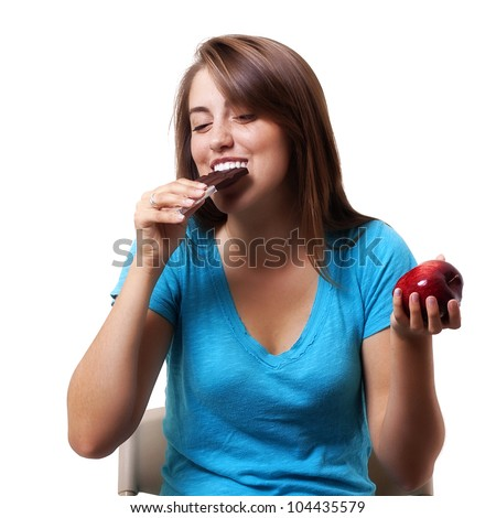 pretty young woman gives into a craving and chooses a chocolate bar over an apple