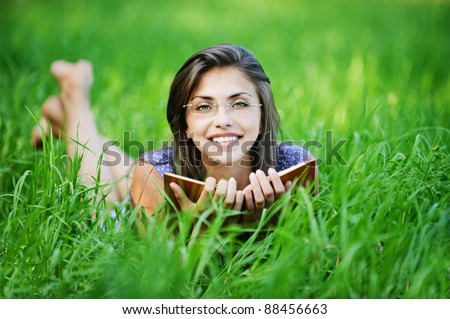 pretty young woman glasses lying green grass reading book background green meadow - stock photo