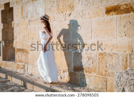 Pretty young woman going near the stone wall - stock photo