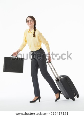 Pretty young woman going with a suitcase, white background