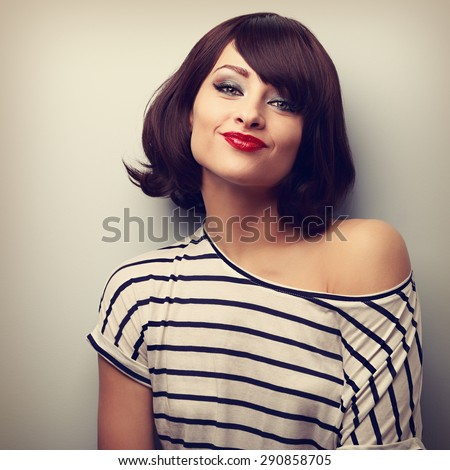 Pretty young woman grimacing with short black hair style in fashion blouse. Vintage closeup portrait - stock photo