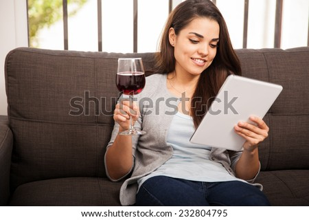 Pretty young woman having a glass of wine while using a tablet computer at home - stock photo