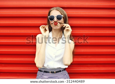 Pretty young woman having fun shows moustache hair over red background - stock photo