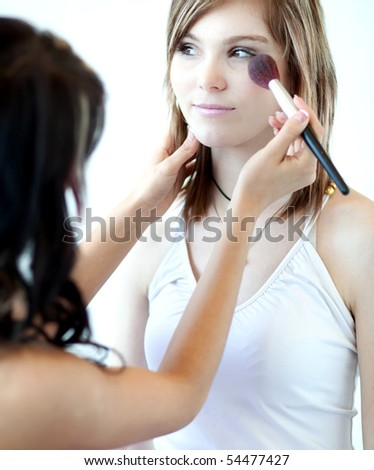 pretty young woman having powder applied by a make-up artist/beautician - stock photo