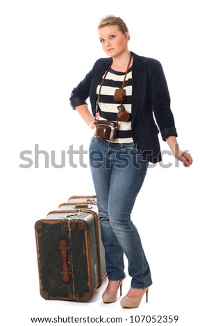 Pretty young woman heading on her travels with vintage camera and travel chest - stock photo