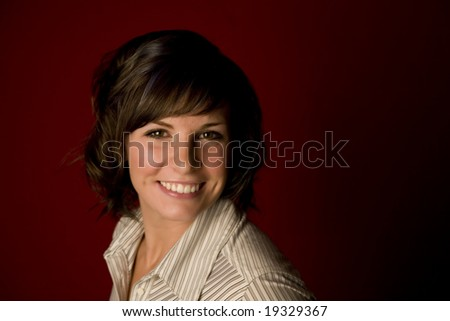 Pretty young woman headshot on red - stock photo