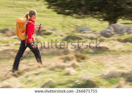 Pretty, young woman hiking in mountains (motion blurred image) - stock photo