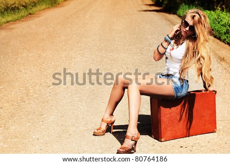 Pretty young woman hitchhiking along a road.