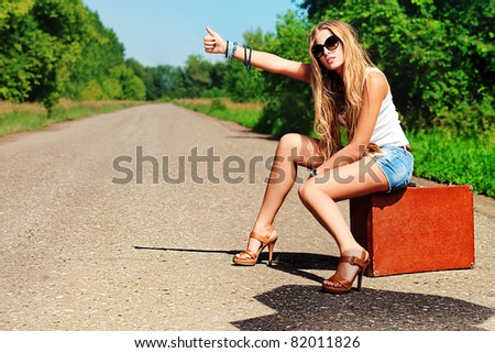 Pretty young woman hitchhiking along a road. - stock photo