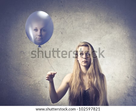 Pretty young woman holding a balloon with her face on it - stock photo